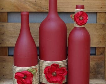 Set of three handpainted burgundy wine bottles with twine and flowers