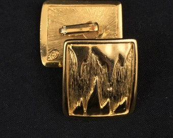 Statement goldtone clip on earrings. Goldtone with relief mountain design signed BG Bergdorf Goodman