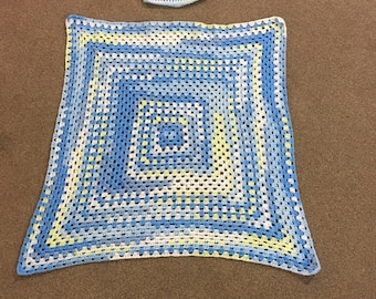 A beautiful blue crocheted baby blanket and matching hat