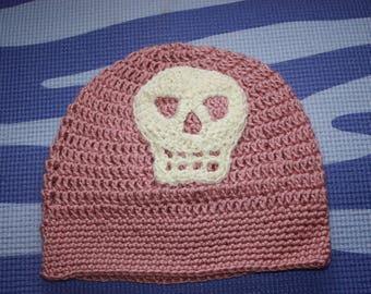 crocheted pink slouchy hat with white skull.