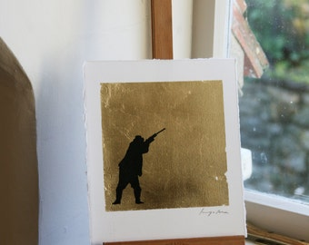 Hand drawn shooting man in pen and ink on gold leaf