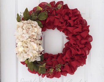 Primitive fall burlap wreath with cream hydrangeas and greenery. Ruffle red burlap wreath with greenery and cream flowers