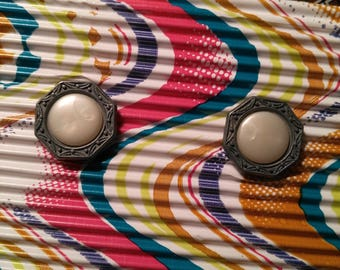 Two buttons. Pearl sits inside these intricate frames of silver.
