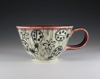Wheel-thrown, purple glazed hand-carved teacup with ladybug design