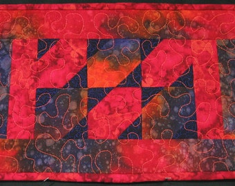 Orange, purple and red batik triangles placemat