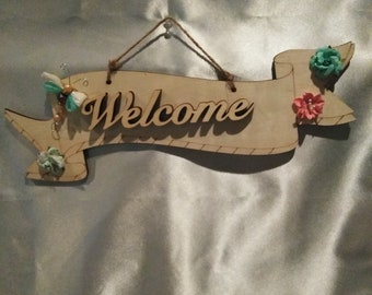 Welcome wooden wall hanging with kanzashi sparkle winged dragonfly. Enhanced with teal and peach flowers. Comes with twine hanger,