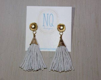 "White beaded tassel earrings, with gold plated studs. Drop length is 2""."