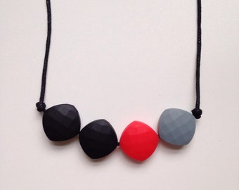 Teething necklace in red, grey and black; made from BPA free chewable silicone quadrate beads by Little Gnashers