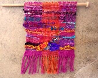 Handwoven, saori style tapestry weaving, wall hanging in pink, blue and orange shades.