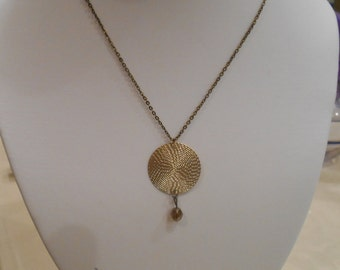 golden disk necklace with glass bead dangle