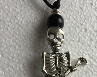 Skeleton with guitar black thong necklace