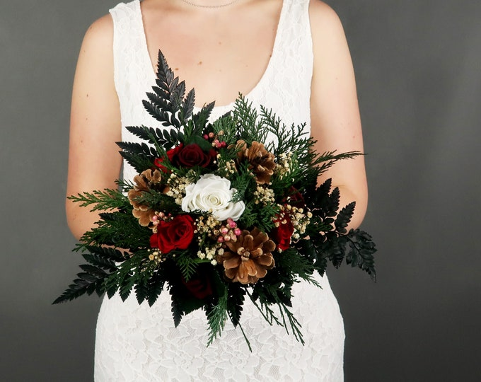 Winter wedding bouquet with pine cones, berries, and real preserved roses