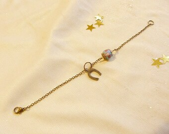 Romantic woman, with chain bracelet, Pearl flower and Horseshoe.