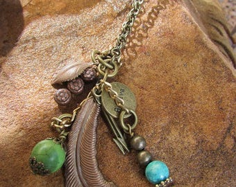 "Handrafted brass necklace adorned with feathers, arrows, turquoise and leafs. Charm necklace. ""Reflection"""