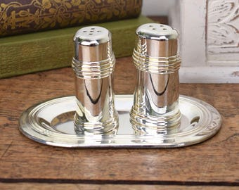 Vintage salt and pepper pots, silver tone metal on matching tray.