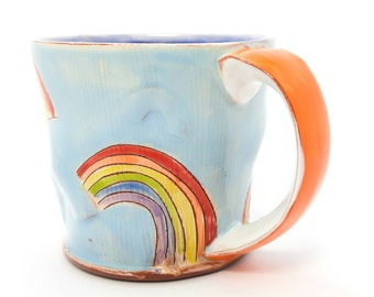 Puffy blue rainbow Earthenware mug. Wheel thrown, food safe mug made by Kaitlyn Brennan. This is a big handmade mug perfect for coffee