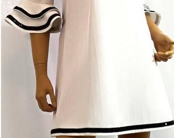 White mini dress whit black sequin trim.