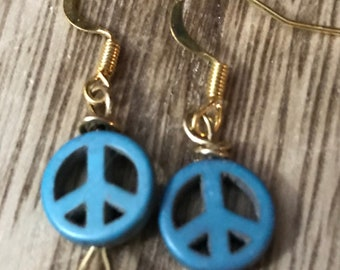 Gold wire wrapped earrings with small, blue peace sign beads.