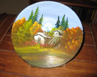 """VINTAGE CABIN PAINTING On A Metal Dish 7"""" Across And 1 1/2"""" High Cabin With Pine Trees And Snow Covered Mountain Signed Nicholas"""