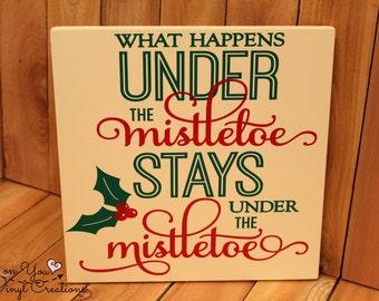 What happens under the mistletoe stays under the mistletoe hanging wood sign / Christmas sign