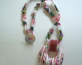 Pink, Lime Green, and White Hollow Donut Pendant with a Bead Woven Necklace by Carol Wilson of PollyClayDesigns
