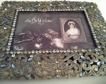 Metal and rhinestone bits on picture frame, with glass