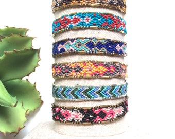 Handwoven beaded friendship bracelets in pink, blue, red, and tan. Embellished woven friendship bracelets