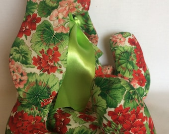 Handmade bunny rabbit made from a fabric of red and pink geraniums outlined in gold lame with lime green satin bow accent