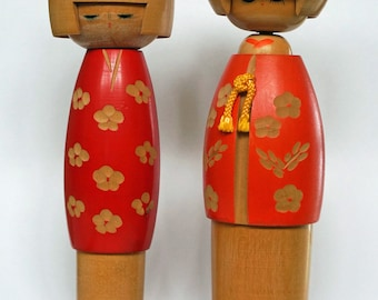 Two Neutral Wood Kokeshi Dolls in Red Floral Kimonos