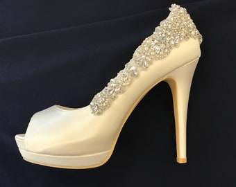 Bridal shoes with open toe design, platform heel, and silver color rhinestones and pearls appliques.