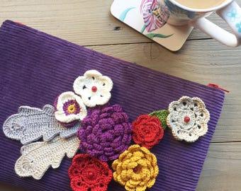 Crochet flowers on velvet clutch