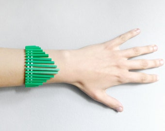 bold geometric bracelet with green lines and white beads , contemporary jewelry