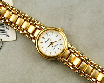 Vintage Acuet NOS watch with gold tone case and bracelet white dial