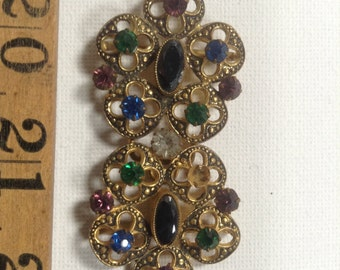 Czech buckle set with numerous rainbow glass stones and set into an ornate filigree metal base