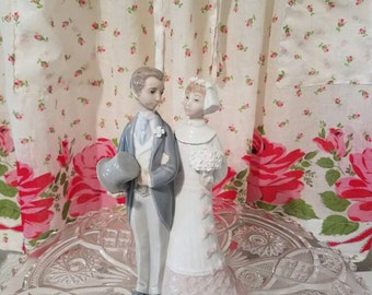 Porcelian Lladro bride and groom wedding cake toppers
