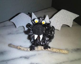Black Halloween bat decorated pinecone