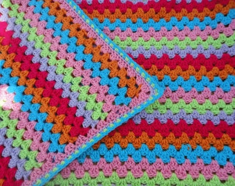 Handmade bright coloured crocheted baby blanket