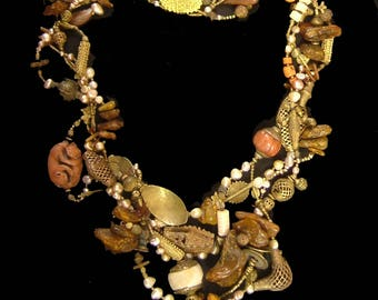 """African brass, Tibetan coral, pearls, amber, golden horn, carnelian, conch, lots of other interesting pieces.  32"""""""