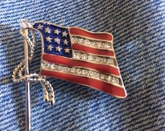 Silver tone enamel and rhinestone waving american flag pin.