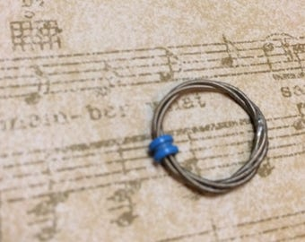 Guitar string midi or childs ring. This ring is a spinner/anxiety ring.
