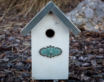 Unique birdhouse with metal roof and turquoise perch