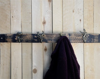 Wall coat rack with hunting themed coat hooks on a repurposed whiskey barrel stave