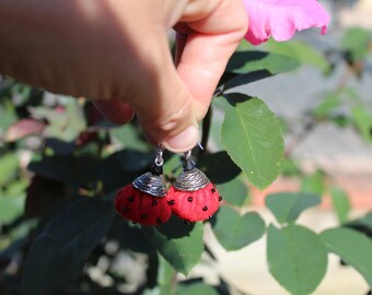 pair of earrings in red felt embellished with black seed beads