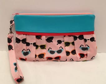 AK31Compleat Clutch: in a fun sunglasses print with pleated front, zipper closure and detatchable hand strap