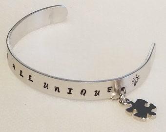 Autism Awareness Puzzle Piece Charm Bracelet - Metal Stamped - WE ARE All UNIQUE. W/ Light Bulb graphic image