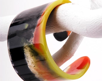 Bangle, resin cuff, black, orange and lemon marbled, fits S