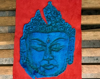 Blue leather burned Buddha patch stitched onto bright red leather