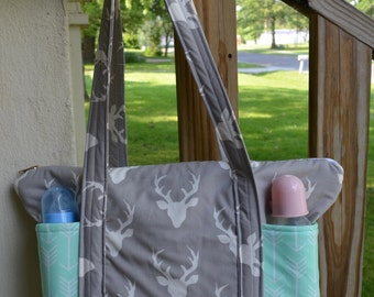 Handmade zip top diaper bag made with buck head silhouette and mint green arrows fabric