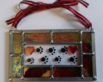 Handmade rectangular fused glass paw print panel with traditional leaded framing.