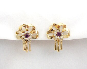 Gilded metal bow shaped vintage earrings embellished with rhinestones and dangles from Fifties